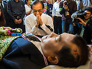 27 JANUARY 2014 - BANGKOK, THAILAND: A man prays after pouring water during the bathing rites for anti-government leader Suthin Taratin at Wat Sommanat Rajavaravihara in Bangkok. In Thai tradition, after death a bathing ceremony takes place in which relatives and friends pour water over one hand of the deceased. Suthin was a core leader of the People's Democratic Force to Overthrow Thaksinism (Pefot), one of several organizations leading protests against the elected government of Thai Prime Minister Yingluck Shinawatra. He was murdered Sunday, Jan. 28, while he was leading a rally to prevent voters from reaching a polling center in the Bang Na district of Bangkok.     PHOTO BY JACK KURTZ