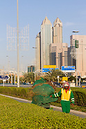 Migrant worker doing garden maintenance along the Corniche in Abu Dhabi, UAE.