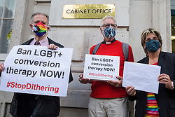 Veteran LGBT+ and human rights campaigner Peter Tatchell (l), Revd Colin Coward (c) and Jayne Ozanne of the Ban Conversion Therapy Coalition (r) prepare to hand in a petition signed by 7,500 people at the Cabinet Office and Government Equalities Office calling on the government to fulfil a promise it made in July 2018 to ban LGBT+ conversion therapy on 23rd June 2021 in London, United Kingdom. LGBT+ conversion treatments, which have been linked to anxiety, depression and self-harm, have been condemned by major UK medical, psychological and counselling organisations.