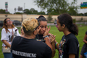 Angel Ayala wipes tears from the face of girlfriend Carla Montanez while grieving the loss of friend Leroy Valentin Fernandez on the one-year anniversary of the mass shooting at Pulse nightclub, from his grave at Greenwood Cemetery in Orlando, Florida, U.S. Montanez's daughter Keila Murillo (R), 13, helps to console her mother.