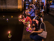 25 NOVEMBER 2015 - BANGKOK, THAILAND: People pray along the shore line of a khlong (canal) before floating their krathongs during Loy Krathong near Wat Yannawa in Bangkok. Loy Krathong takes place on the evening of the full moon of the 12th month in the traditional Thai lunar calendar. In the western calendar this usually falls in November. Loy means 'to float', while krathong refers to the usually lotus-shaped container which floats on the water. Traditional krathongs are made of the layers of the trunk of a banana tree or a spider lily plant. Now, many people use krathongs of baked bread which disintegrate in the water and feed the fish. A krathong is decorated with elaborately folded banana leaves, incense sticks, and a candle. A small coin is sometimes included as an offering to the river spirits. On the night of the full moon, Thais launch their krathong on a river, canal or a pond, making a wish as they do so.     PHOTO BY JACK KURTZ