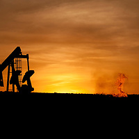 An oil well jack pump and natural gas flare off at sunset in the Bakken oil field north of Williston, North Dakota.