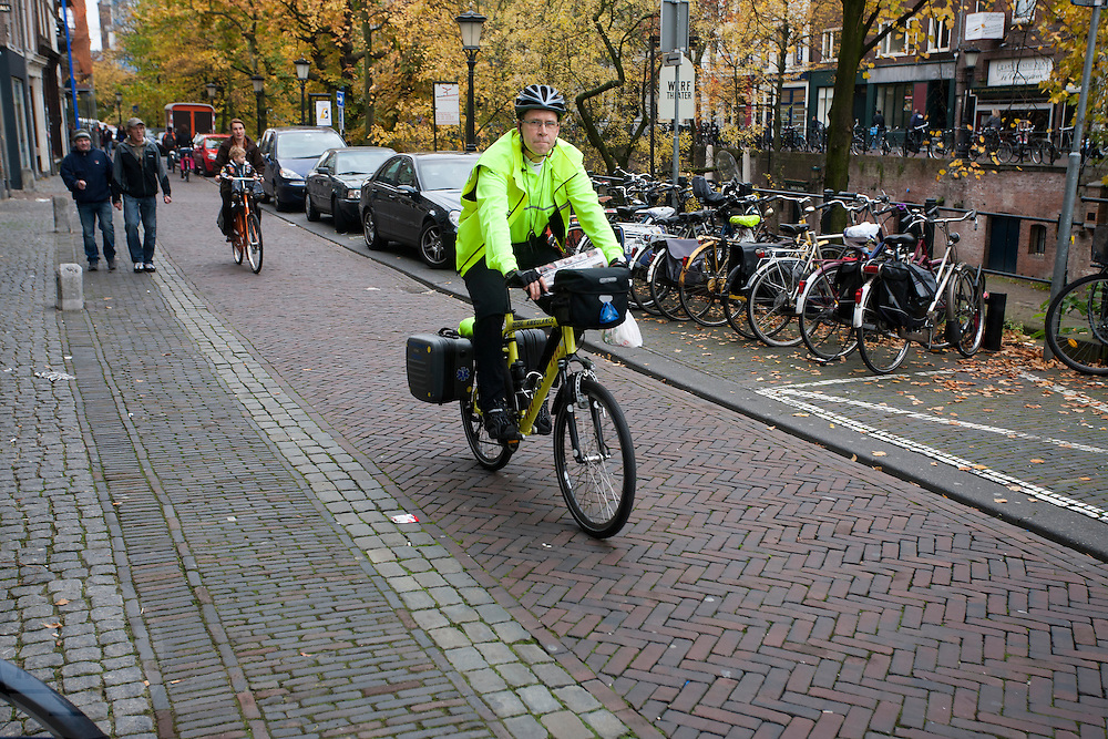 Een medewerker van de ambulancedienst RAVU rijdt op de ambulancefiets over de Oudegracht in Utrecht.<br /> <br /> An employee of the RAVU, the first aid service, is riding the special ambulance bike.
