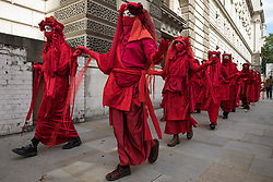 Members of the Red Rebel Brigade leave the Back The Bill rally by fellow climate activists from Extinction Rebellion in Parliament Square on 1st September 2020 in London, United Kingdom. Extinction Rebellion activists are attending a series of September Rebellion protests around the UK to call on politicians to back the Climate and Ecological Emergency Bill (CEE Bill) which requires, among other measures, a serious plan to deal with the UK's share of emissions and to halt critical rises in global temperatures and for ordinary people to be involved in future environmental planning by means of a Citizens' Assembly.