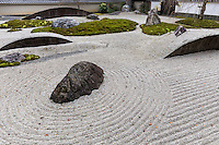 The stone garden of Jisso-in has a number of modern features that make it unique among Zen gardens. Jisso-in makes use of large moon shaped stones that appear as though they are submerged below the gravel. Looking like giant ocean waves, these man-made stones rise up alongside the garden's mossy island and formed stones. The garden has a surrounding wall that is lined with trees, and its unusual elements contribute to the garden's elegance.