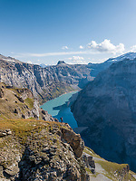 Aerial View of hiker on the side of cliff in Swiss Mountain Lake in Glarus, Switzerland.