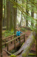 Young woman hiking along the Upper McKenzie River  OR.
