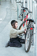 Israel, Jerusalem, Mea Shearim neighbourhood, Jewish religious boy fixing bicycle