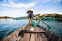 A woman rows a boat along the Thu Bon river in Hoi An, Vietnam. Hoi An is a UNESCO-recognized World Heritage Site, and a popular tourist destination in Vietnam.