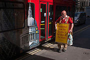 A Christian alongside a London tour bus carries a sandwich board quoting the words of Ecclesiastes 12.1 with the Biblical message that youth should remember their creator.