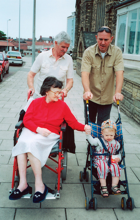 Extended family of grandmother; grandfather; father & grandson in buggy out walking, Grandmother disabled in wheelchair, UK