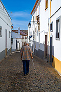 Old man walking with cane in typical street scene of white and yellow houses, lanterns, narrow cobble street in Evora, Portugal
