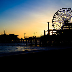 Photo of Santa Monica Pier sunset in Southern California. Santa Monica Pier is a landmark located in Los Angeles county that has an amusement park with a ferris wheel, roller coaster, restaurants, and other attractions.