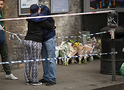 © Licensed to London News Pictures. 17/10/2017. London, UK. People believed to be friends and relatives of the victim hug after placing floral tributes near the crime scene. Police are investigating after a man in his 20's was stabbed to death and two others were injured in an incident on Monday night outside Parsons Green underground station a terrorist attack took place last month. Photo credit: Peter Macdiarmid/LNP