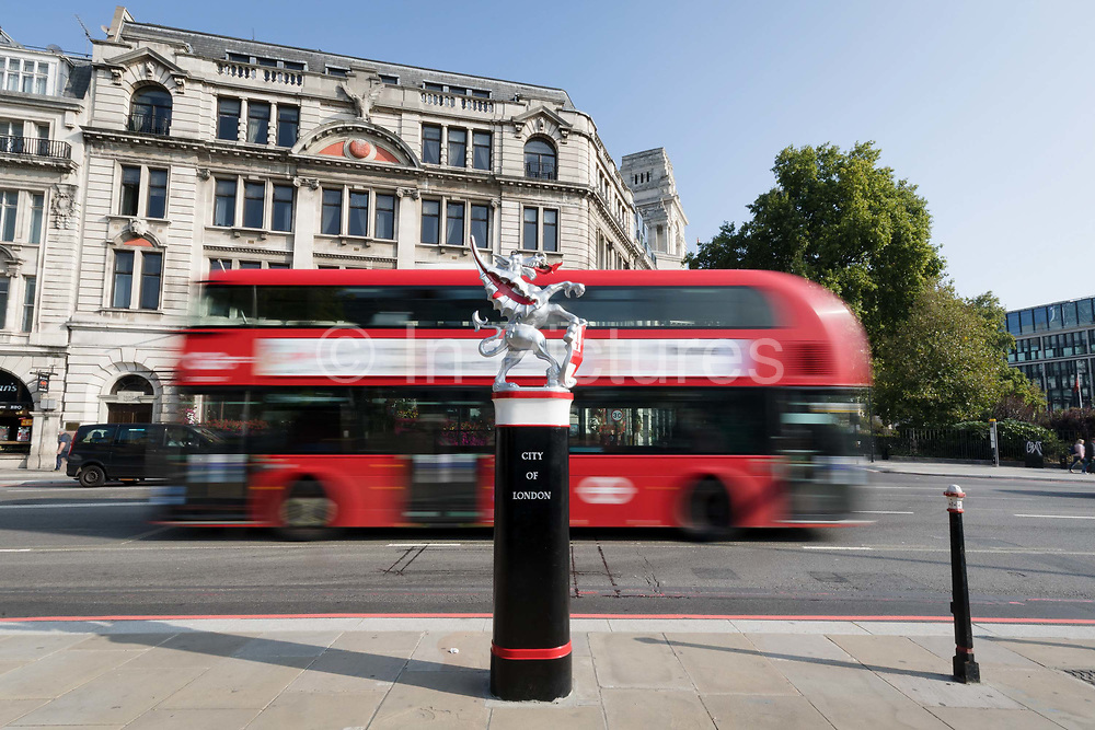 A City of London dragon boundary mark bollard on the border of Tower Hamlets as a red double decker bus passes on Lower Thames Street on September 06, 2018. Thedragon boundary marksarecast ironstatues ofdragonson metal or stone plinths that mark the boundaries of theCity of London painted silver, with details of the dragon wings and tongue picked out in red.