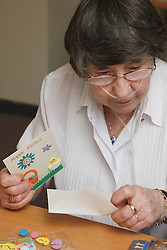Person dependent on oxygen supplied by nasal tubes doing a craft activity at a resource for people with physical and sensory impairment.