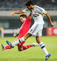 Zhang Linpeng of China, left, tries to block a shot by Roque Santa Cruz of Paraguay during a friendly football match in Changsha city, central China's Hunan province, 14 October 2014.<br /> <br /> Paraguay's dismal run of form continued as they suffered a 2-1 friendly defeat to China on Tuesday (14 October 2014). The South American nation, who came into the game having won two of their previous 13 fixtures, fell short in their bid to pull off a late comeback at Changsha's Helong Stadium. In contrast to their opponents, China have now lost just two of their last 16 matches as they continue to build towards next year's AFC Asian Cup in Australia.