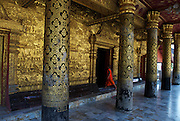 A young novice monk enters the buddhist temple of Wat Mai, via its eleborately decorated golden portico. In the late 1800s, French colonial powers and the Lao aristocracy of Vientiane developed a new architectural fusion in Luang Prabang, inspired by local temples and materials, and French and Indochine architecture. The French brought in skilled Vietnamese builders to build two-storey villas throughout the town.