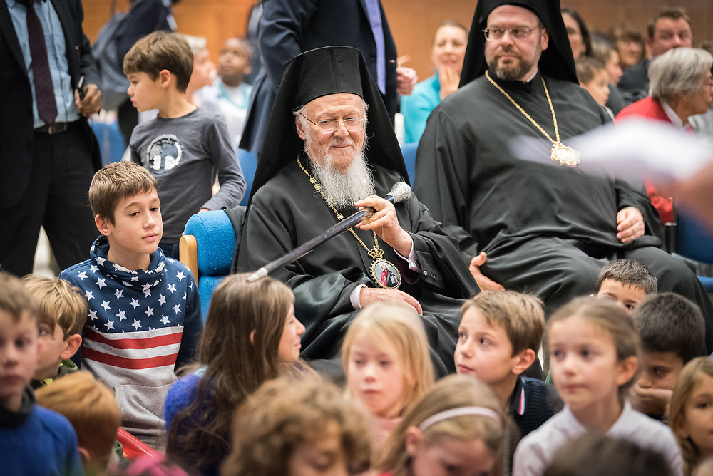 """21 November 2018, Geneva, Switzerland: Ecumenical Patriarch Bartholomew teases a girl as he joins school children from the Greek schools in Geneva and Lausanne to watch a puppet show at the Ecumenical Centre. On the occasion of 2018 World Children's Day, and in recognition of the World Council of Churches' 70th anniversary, UNICEF and WCC convene a number of WCC member churches and common partners to celebrate the UNICEF-WCC global partnership and to take stock of the many achievements of the Churches' Commitments to Children. In line with the spirit of a day """"for children, by children,"""" the celebratory event placed children at the centre by asking them to share their recent experiences as participants in the several Youth Talks on ending violence in schools that WCC member churches around the world have organized in recent years; hearing the perspective of young migrants supported by a church-run sponsorship project; and showcasing promising examples of how churches support children in climate justice activities."""