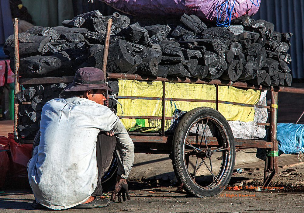 Dark and Dirty: A man rests from his labours as he squats down in the street beside his charcoal filled  cart, Phnom Penh, Cambodia.