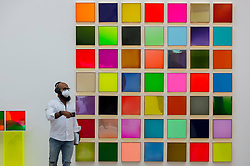 """© Licensed to London News Pictures. 21/10/2020. LONDON, UK. A visitor passes """"Fragments"""", 2020, by British artist Nat Bowen.  Bowen uses the study of Chromology, the psychology behind colour, as a way to communicate non verbally through her work. Preview of STARTnet Art Fair at the Saatchi Gallery in Chelsea.  The contemporary art fair showcases local London, as well as international, galleries and individual artists from all over the world.  The fair runs 21 to 25 October with Covid-19 protocols in place for visitors.   Photo credit: Stephen Chung/LNP"""
