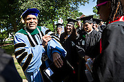 President of Grinnell College Raynard Kington shows off his presidential robes to students waiting to process into the graduation area. He explains that the fourth stripe on the robes is reserved especially for college presidents. BEN BREWER/Grinnell College