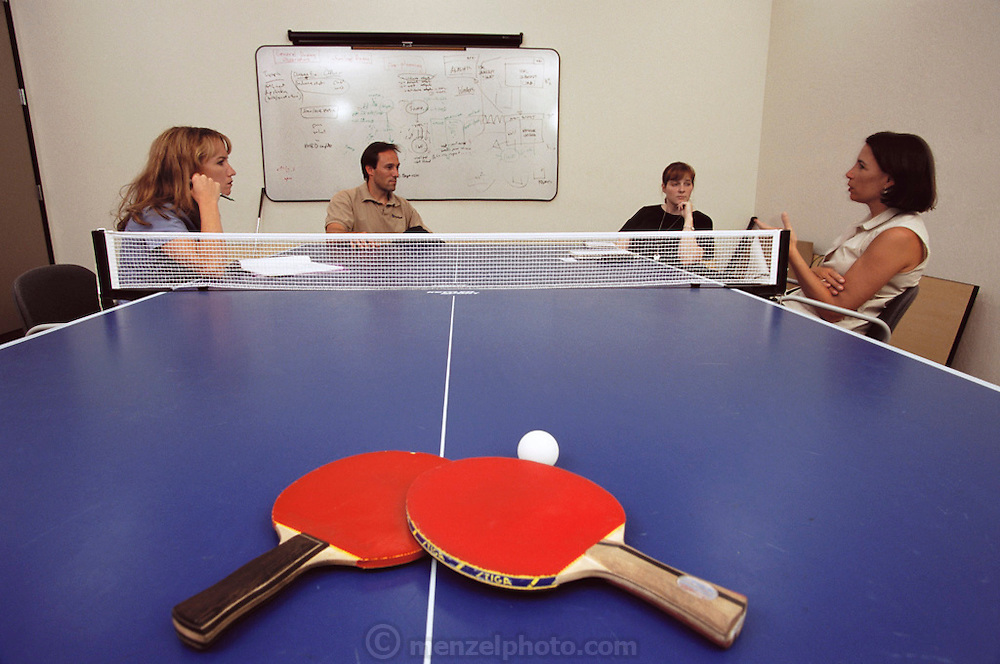"""Silicon Valley, California; Icarian Corporation Software; 4 PM: CEO Doug Merritt meets with three employees to strategize on an internal program to instill company values in their employees. The ping pong table they are meeting over was Icarian's first meeting table. All of Icarian's employees are ranked according to their ping-pong ability and there is a """"ladder"""" of their ranking posted on the web. (1999)."""