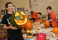 Ryan Steele shows off his craftsmanship in pumpkin carving in Jane Connelly's 7th grade classroom at Laconia Middle School.  Approximately 400 pumpkins will be carved by students to add to the Tower at Pumpkin Fest on Saturday.  (Karen Bobotas/for the Laconia Daily Sun)