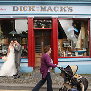 A couple celebrate their marriage with a pint of Guinness outside Dick Mack's pub, a famous pub in Dingle, County Kerry, Ireland. Dingle is the only town on the Dingle Peninsula. Principal industries in the town are tourism, fishing and agriculture. Dingle, County Kerry, Ireland. Photo Tim Clayton