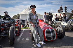 **CAPTION CORRECTION. Picture originally sent with wrong date. Picture was taken TODAY 11/09/2015** © licensed to London News Pictures. 11/09/2015<br /> Goodwood Revival Weekend, Goodwood, West Sussex. UK.<br /> The Goodwood Revival is the world's largest historic motor racing event. Competitors and enthusiasts dress in period fashions recreating the glorious days of the race circuit.<br /> Pictured Mechanic Sabina from Germany next to a 1948 Maseratti.<br /> <br /> Photo credit : Ian Whittaker/LNP