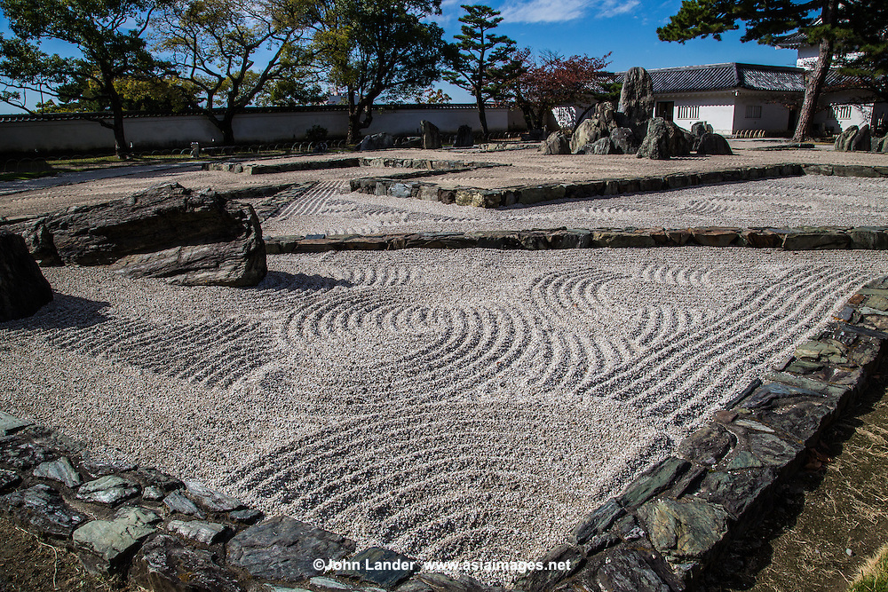 """Hachijin-no-Niwa Garden at Kishiwada Castle - a very unique karesansui garden  set in the courtyard of Kishiwada-jo and designed to be viewed from the windows of the castle. It is a very modern design of geometric, linear stones punctuated by rocks in a field of pebbles. The garden was designed by Mirei Shigemori, a leading figure in the development of the modern Japanese garden. Eight groups of rocks represent the """"Battle Formation of the Eight Positions"""". Each of these eight groupings has a name: heaven, earth, phoenix, dragon, cloud, serpent, tiger and wind.  The garden challenges our thinking about the usually calm effect of stone gardens. Based on the layout of a mythological battle conducted by Chinese General Zhuge Liang, the stone setting at the center of the design, named Central Camp, is the garden's focal point."""