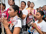"""23 JUNE 2015 - MAHACHAI, SAMUT SAKHON, THAILAND: People pray as the City Pillar Shrine is brought to a waiting fishing boat in Mahachai. The Chaopho Lak Mueang Procession (City Pillar Shrine Procession) is a religious festival that takes place in June in front of city hall in Mahachai. The """"Chaopho Lak Mueang"""" is  placed on a fishing boat and taken across the Tha Chin River from Talat Maha Chai to Tha Chalom in the area of Wat Suwannaram and then paraded through the community before returning to the temple in Mahachai.   PHOTO BY JACK KURTZ"""