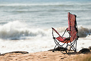 A red and white striped beach chair sits empty on the southwestern beaches of Kauai, Hawaii.