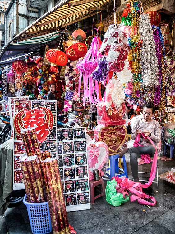 Seller sits in a shop filled with votive paper goods along Hang Ma street, famous for these products in Hanoi's Old Quarter, Vietnam, Southeast Asia