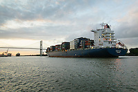 A cargo ship navagates to pass under the Talmadge Memorial Bridge in Savannah, Georgia at sunset..