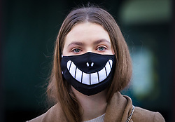 March 16, 2020, London, UK: A woman commuter wearing a face mask with a smile on walks near Bank in the City of London this morning. New cases and fatalities resulting from the COVID-19 strain of the Coronavirus continue to be reported daily in the UK with major sporting fixtures cancelled and people advised to stay at home if they have a cough and high temperature. (Credit Image: © Vickie Flores/London News Pictures via ZUMA Wire)