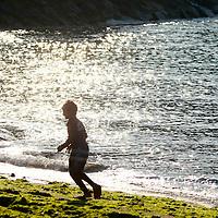 Young boy runs along the beach at East Coast Park, Singapore.