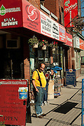 A shopkeeper in a yellow shirt stands in front of a hardware store on Toronto's Queen Street East.