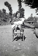 young girl sitting and holding a small goat rural France 1950s