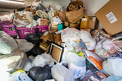© Licensed to London News Pictures. 22/03/2020. London, UK. Overflowing domestic rubbish bins are seen in the communal bin room of a block of flats in east London today, as the coronavirus outbreak continues to escalate in the capital. Recent media reports have stated that some local councils plan to cancel certain types of rubbish collections to help stop the spread of coronavirus. Photo credit: Vickie Flores/LNP