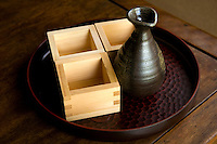 Traditionally, sake is served in wooden box cups known as masu with a standard measurement of  180 ml or 6 fl oz.  These tiny cedar  box cups were thought to complement the taste of sake. Tradition requires the masu be filled to the rim as a sign of prosperity.  Nowadays, sake is more typically served in ceramic cups. The cups used for drinking sake tiny vessels called ochoko.  While not a traditional serving glass a shot glass is also sometimes used.