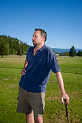 Man leaning on golf club at Eagle Bend golf course in Bigfork, Montana.