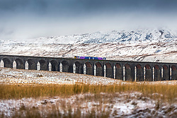 © Licensed to London News Pictures. 28/01/2020. Ribblehead UK. A commuter train crosses Ribblehead viaduct this morning in the shadow of snow covered Whernside mountain in the Yorkshire Dales. Photo credit: Andrew McCaren/LNP