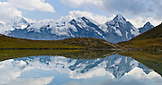 """Gspaltenhorn (3437 meters) reflects in Grauseeli lake on Schilthorn mountain near Birg cable car station in the Berner Oberland, Switzerland, the Alps, Europe. UNESCO lists """"Swiss Alps Jungfrau-Aletsch"""" as a World Heritage Area (2001, 2007). Panorama stitched from 2 overlapping images."""