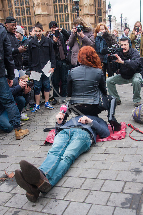 London, December 12th 2014. Porn and sex workers gather outside the Houses of Parliament for a mass sex simulation and face-sitting event in rotest against newly outlawed sex acts in the making of pornography in the UK. Under new Audiovisual Media Services Regulations 2014 rules, such acts as facesitting, spanking and female ejaculation are, among others, now banned from being shown  porn watched online. PICTURED: A woman face-sits a TV reporter.