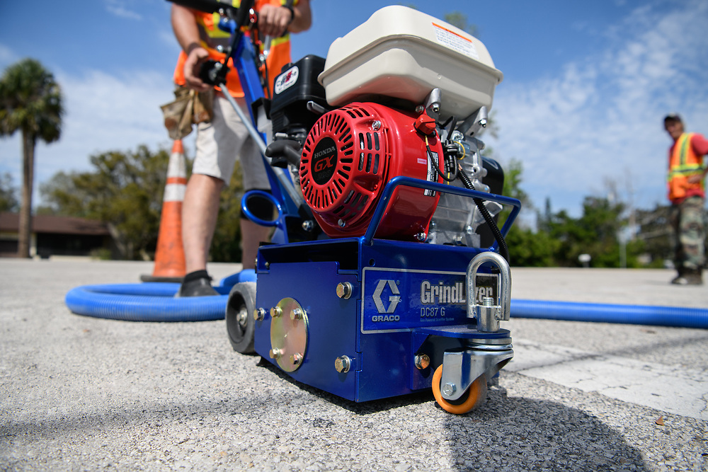 Worker using a Graco Grindlaser on a street in Florida