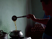 Bhutanese woman making tea in Radhi village, Eastern Bhutan