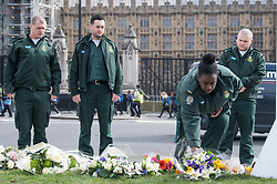 © Licensed to London News Pictures. 22/03/2018. London, UK. A group of ambulance workers place flowers on Parliament Square, outside the Houses of Parliament in Westminster, London on the one year anniversary of the Westminster Bridge Terror attack in which lone terrorist killed 5 people and injured several more, in an attack using a car and a knife. The attacker, 52-year-old Briton Khalid Masood, managed to gain entry to the grounds of the Houses of Parliament and killed police officer Keith Palmer. Photo credit: Ben Cawthra/LNP