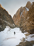 A man walks in a Gorge.<br /> <br /> Travels in the Gobi desert region.<br /> In and around the Yolyn Am gorge in the Gurvan Saikhan Mountains of Mongolia. The valley is named after the Lammergeier, which is called Yol in Mongolian.
