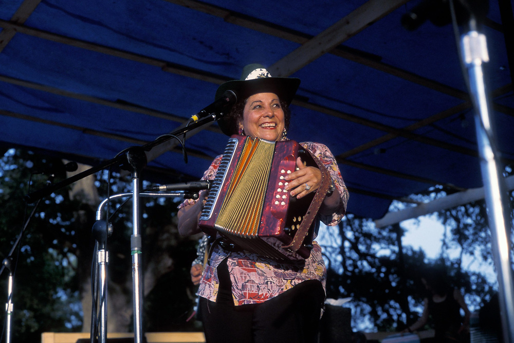 """Hispanic woman playing """"Conjunto""""-style Texas-Mexican blend music on accordian on stage.  ©Bob Daemmrich"""
